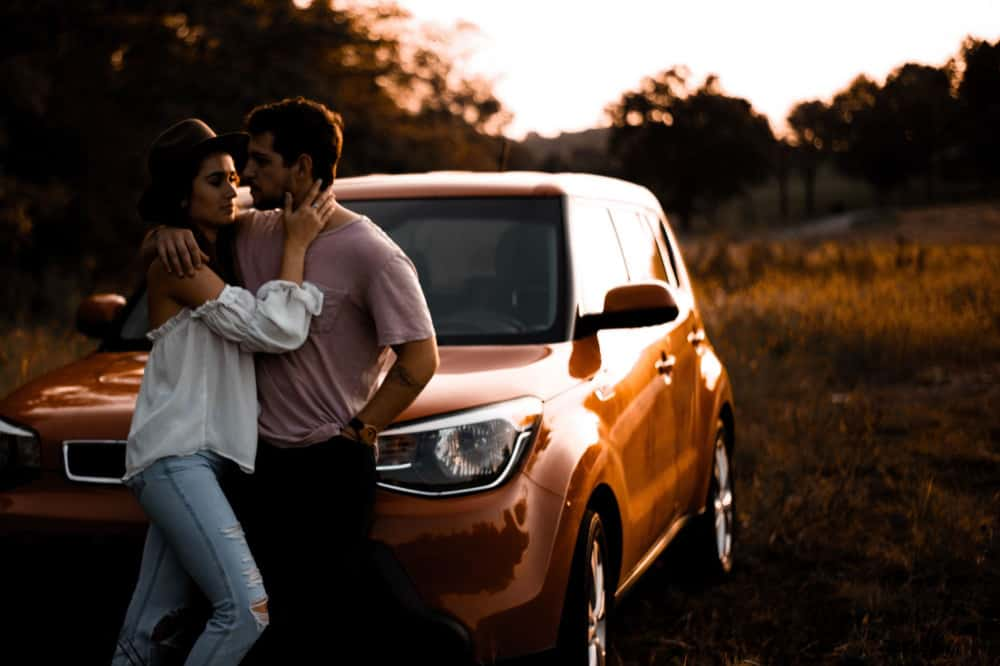 Woman and man in love sitting on their car bonnet
